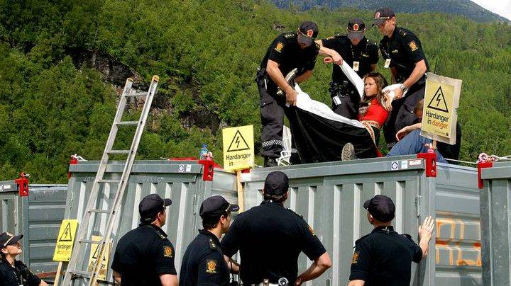 Sju politifolk i sving for få bunadskledde Synnøve Kvamme ned frå containeren.